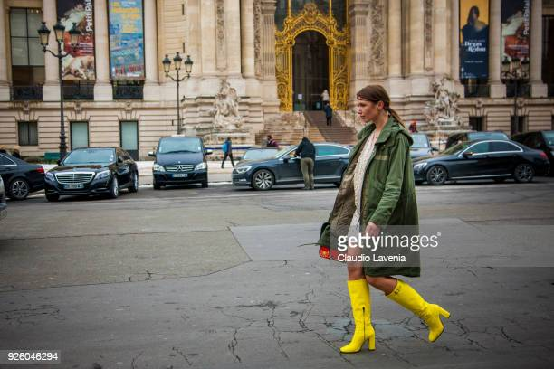 Landiana Cerciu wearing a green parka and yellow heels boots is seen in the streets of Paris before the Paco Rabanne show during Paris Fashion Week...