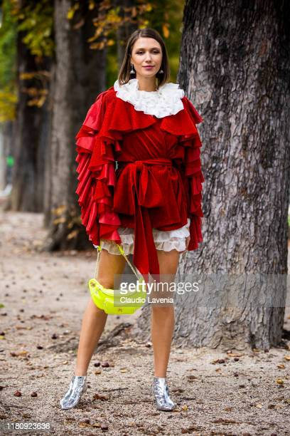 Landiana Cerciu wearing a red decorated jacket neon yellow bag and silver shoes is seen outside the Elie Saab show during Paris Fashion Week...