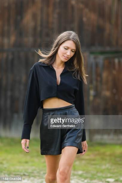 Landiana Cerciu wears a black long sleeves / V-neck crop-top, black leather shorts, on July 22, 2021 in Sibiu, Romania.