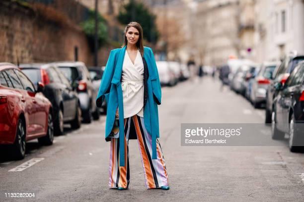 Landiana Cerciu wears a blue coat a white kimono dress multicolor flared striped pants outside Elie Saab during Paris Fashion Week Womenswear...