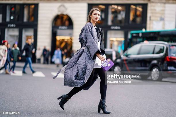 Landiana Cerciu wears a grey padded oversize coat a white top with a black bow a colorful clutch black ankle boots outside Stella McCartney during...