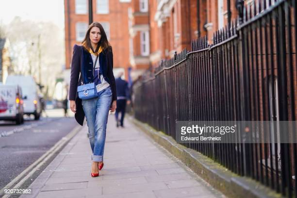 Landiana Cerciu wears a jacket a blue Furla bag blue jeans red shoes during London Fashion Week February 2018 on February 17 2018 in London England