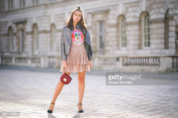 Landiana Cerciu wears a leather jacket a ruffled pink dress with lace a red bag during London Fashion Week February 2018 on February 16 2018 in...