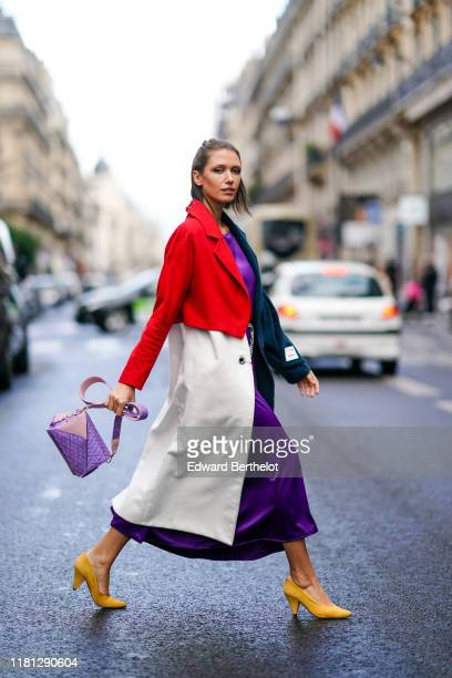 Landiana Cerciu wears a lustrous purple flowing dress, a chain belt, yellow heels, a red, petrol-blue and white coat, a pale pink and light purple...