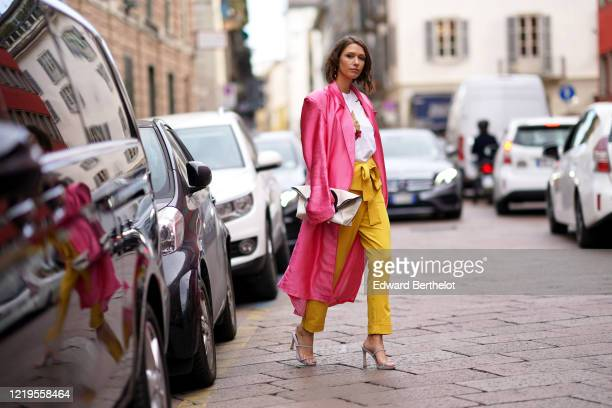 Landiana Cerciu wears a neon pink lustrous silky long coat, a white t-shirt, a bag, yellow pants, gray shoes, outside Tod's, during Milan Fashion...
