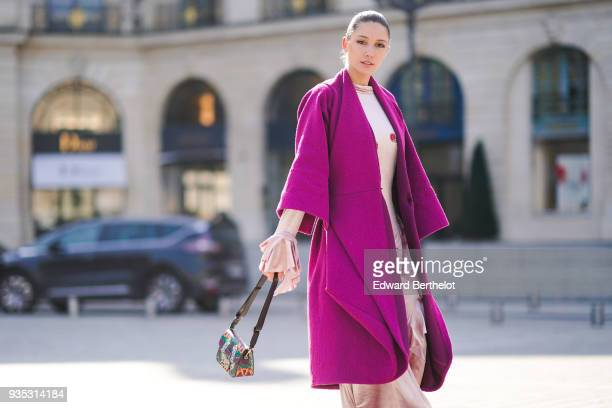 Landiana Cerciu wears a pale pink fulllength flounceside dress with flounce at the sleeves end a fuchsia pagoda sleeves coat a colorful handbag...