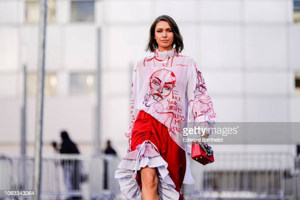Landiana Cerciu wears a pink and red ruffled dress with printed drawings depicting a face a woman's body outside Chloe during Paris Fashion Week...