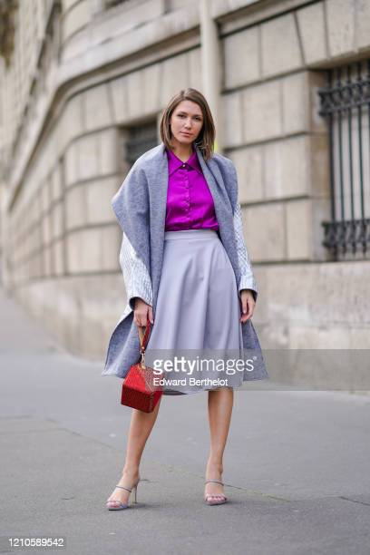 Landiana Cerciu wears a purple lustrous shirt a long checked coat a gray large wool scarf a gray skirt a red cube shaped bag high heeled shoes...