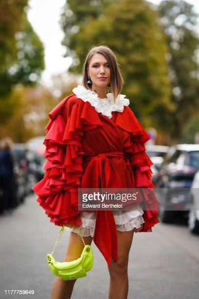 Landiana Cerciu wears a red and white ruffled oversized dress, a neon yellow fanny pack bag, earrings, outside Elie Saab, during Paris Fashion Week -...