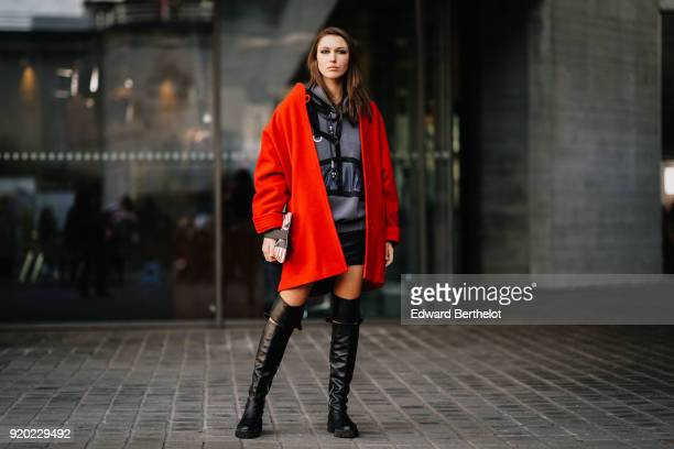 Landiana Cerciu wears a red coat a red striped bag a gray hoodie sweater black leather thigh high boots during London Fashion Week February 2018 on...