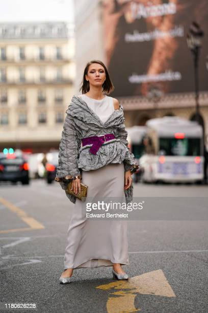 Landiana Cerciu wears a white long dress, a long sleeves off-the-shoulder grey embossed fabric jacket with a tail, a glittering purple belt, grey...