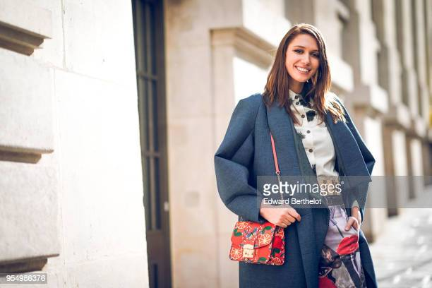 Landiana Cerciu wears a white shirt with black patterns a petrolblue roundedges kimonostyle coat a golden belt a red shoulderbag with colorful...