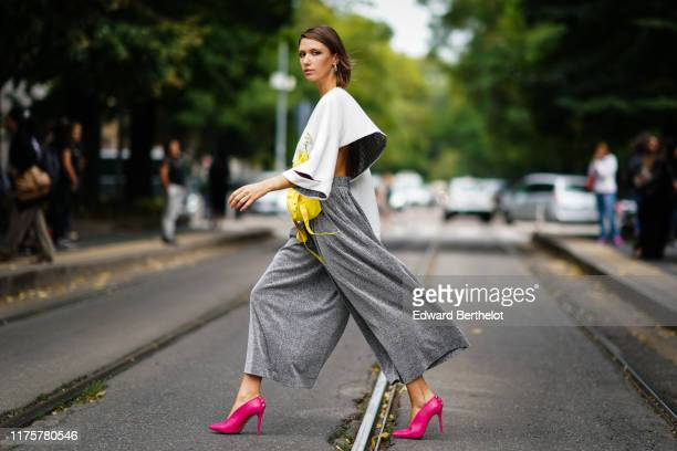 Landiana Cerciu wears earrings, a white flowing cropped top, a yellow bag, gray oversized flare pants, pink heeled shoes, outside the Fendi show...