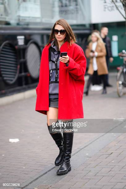 Landiana Cerciu wears sunglasses a red coat a gray hoodie sweater black leather boots during London Fashion Week February 2018 on February 18 2018 in...