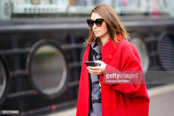 Landiana Cerciu wears sunglasses a red coat holds a smartphone during London Fashion Week February 2018 on February 18 2018 in London England