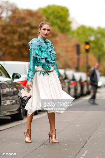 Landiana wears a blue lace ruffle top a white skirt heels shoes outside Valentino during Paris Fashion Week Womenswear Spring/Summer 2018 on October...