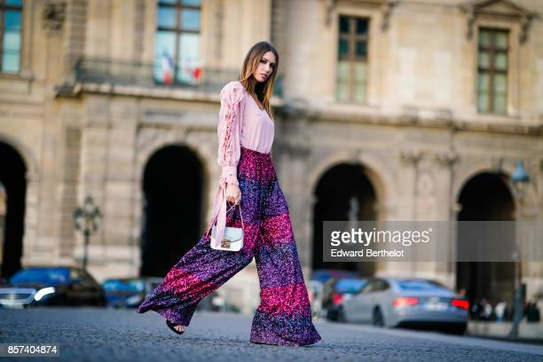 Landiana wears a pink top purple striped shiny pants a bag outside Louis Vuitton during Paris Fashion Week Womenswear Spring/Summer 2018 on October 3...
