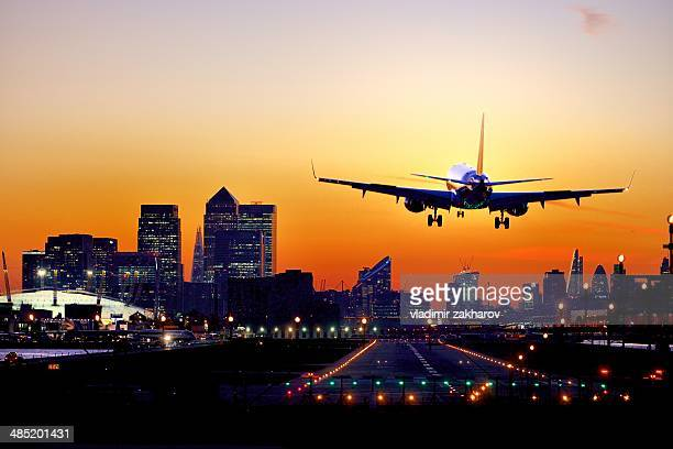 Landing airplane and London skyline at sunset