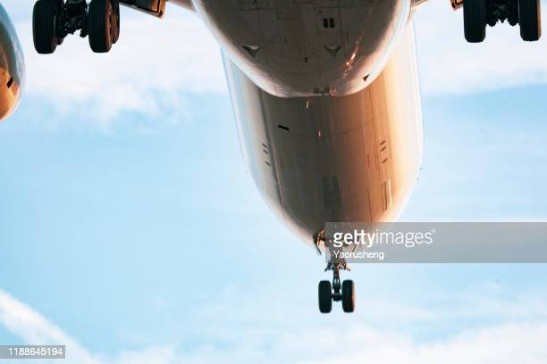 a landing airplane approach the airport - wheel stock pictures, royalty-free photos & images