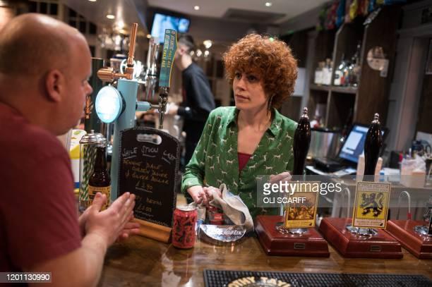 Landlady Abigail Bennett works behind the bar in the communityowned Ye Olde Cross pub in Ryton village near Newcastle upon Tyne in north east England...