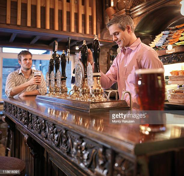 Landlord and customer in English pub