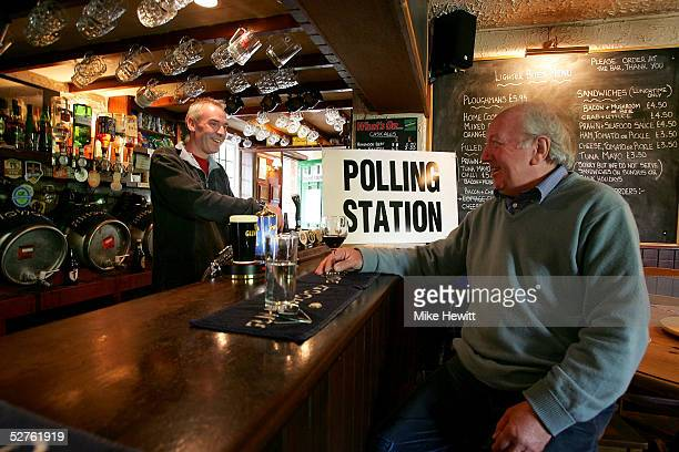 Landlord Nigel Burt serves a customer in The Tichborne Arms doubling as polling station on May 5 2005 in Tichborne Hampshire Voting in the general...
