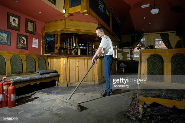 Landlord of the Plough pub Andrew Rogerson sweeps dried mud off the floor of his damaged property in Catcliffe Sheffield UK on Tuesday Aug 7 2007 Six...