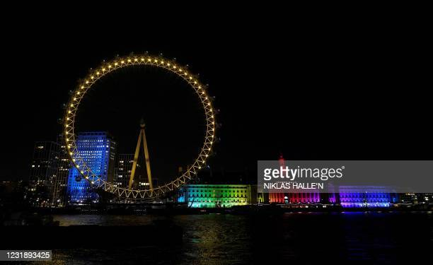 Landmark and tourist attraction The London Eye is illuminated in yellow light as part of the National Day of Reflection on the anniversary of the...