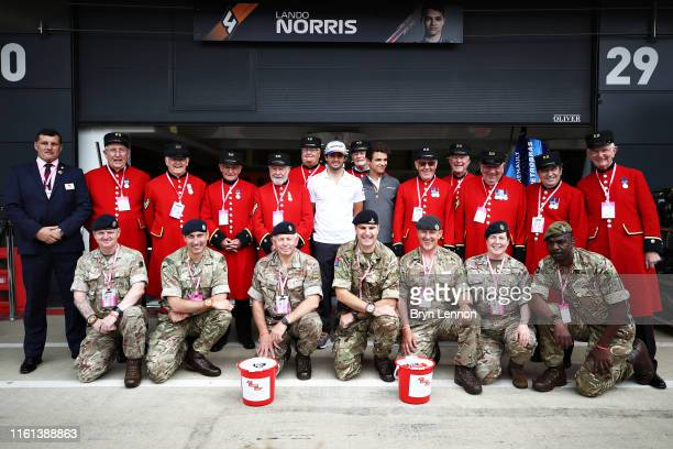 Lando Norris of Great Britain and McLaren F1 and Carlos Sainz of Spain and McLaren F1 pose for a photo with members of the Army Soldiers Charity and...