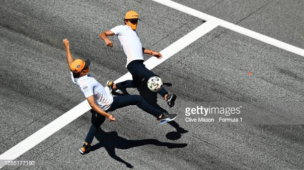 Lando Norris of Great Britain and McLaren F1 and Carlos Sainz of Spain and McLaren F1 play football on the start finish straight during previews for...