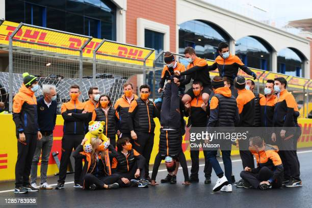 Lando Norris of Great Britain and McLaren F1 and team members pose with a Pudsey Bear toy on the grid after the F1 Grand Prix of Turkey at Intercity...