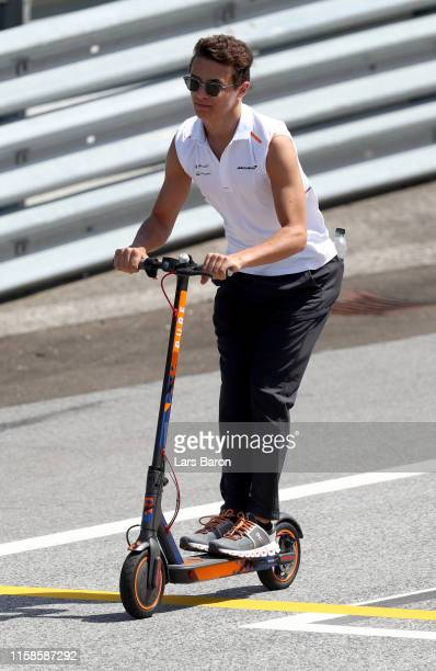 Lando Norris of Great Britain and McLaren F1 rides a scooter around the circuit during previews ahead of the F1 Grand Prix of Austria at Red Bull...