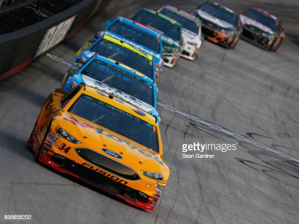 Landon Cassill driver of the Love's Travel Stops Ford leads a pack of cars during the Monster Energy NASCAR Cup Series Bass Pro Shops NRA Night Race...