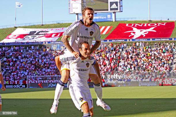 Landon Donovan and David Beckham of the Los Angeles Galaxy celebrate scoring a goal against Chivas USA during Game One of the MLS Western Conference...