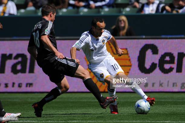 Landon Donovan of Los Angeles Galaxy fights for the ball with Devon McTavish of DC United at the Home Depot Center on March 22 2009 in Carson...