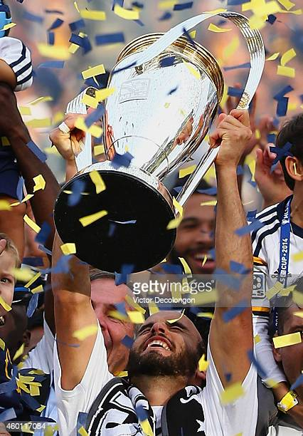 Landon Donovan of the Los Angeles Galaxy celebrates with the Philip F Anschutz Trophy on the podium after the Galaxy defeated the New England...
