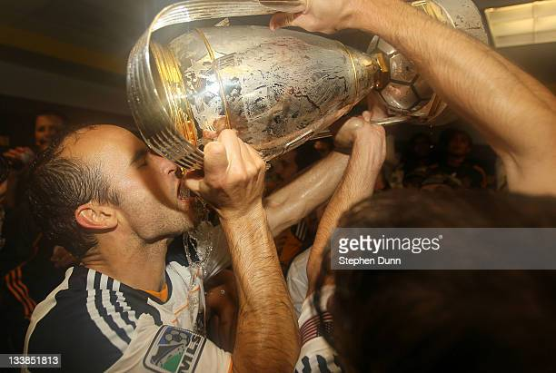 Landon Donovan of the Los Angeles Galaxy drinks from the Philip F Anschutz Trophy in the locker room after defeating the Houston Dynamo 10 in the...
