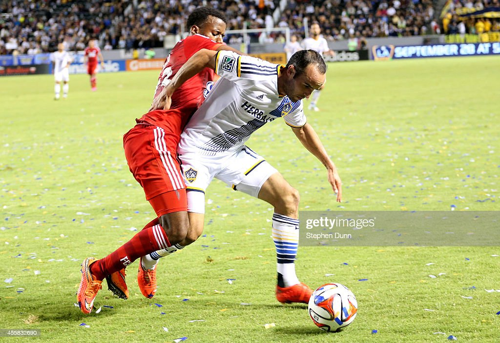 Landon Donovan #10 of the Los Angeles Galaxy is brought down by Kellyn Acosta #23 of FC Dallas at StubHub Center on September 20, 2014 in Los Angeles, California.