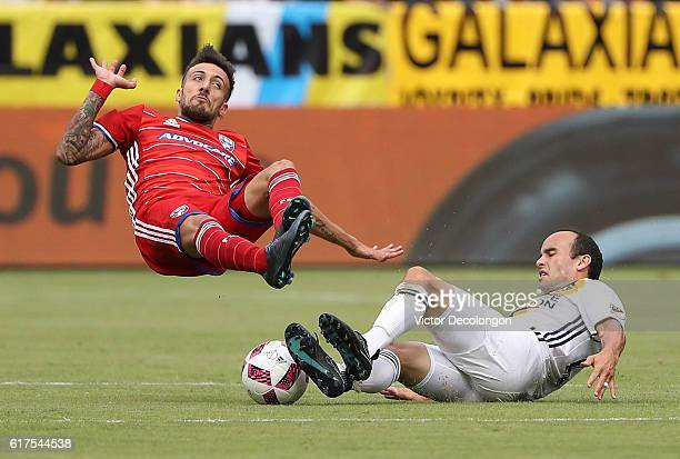 Landon Donovan of the Los Angeles Galaxy tackles Maximiliano Urruti of FC Dallas during the MLS match at StubHub Center on October 23 2016 in Carson...