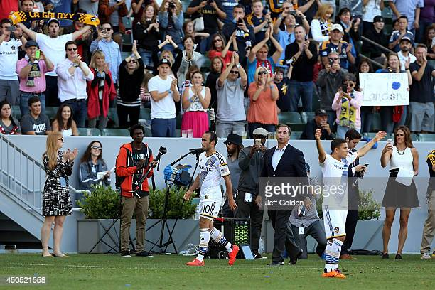 Landon Donovan of the Los Angeles Galaxy walks to the bench to a standing ovation followed by head coach Bruce Arena after being substituted out...