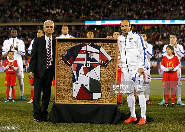 Landon Donovan of the United States reacts with Sunil Gulati president of the United States Soccer Federation as he receives a gift during a ceremony...