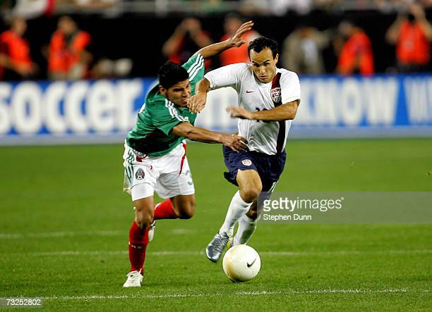 Landon Donovan of the USA gets past Carlos Salcido of Mexico on his way to scoring his team's second goal in the nintyfirst minute of their...
