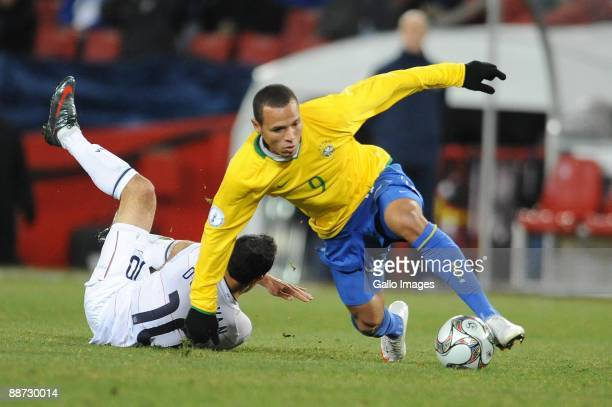 Landon Donovan of USA and Luis Fabiano of Brazil compete during the 2009 Confederations Cup final match between Brazil and USA from Ellis Park on...