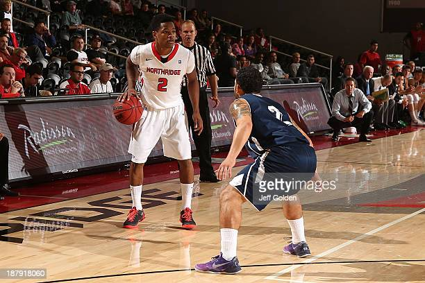 Landon Drew of the Cal State Northridge Matadors dribbles the ball against Matt Green of the Hope International Royals during the second half of the...