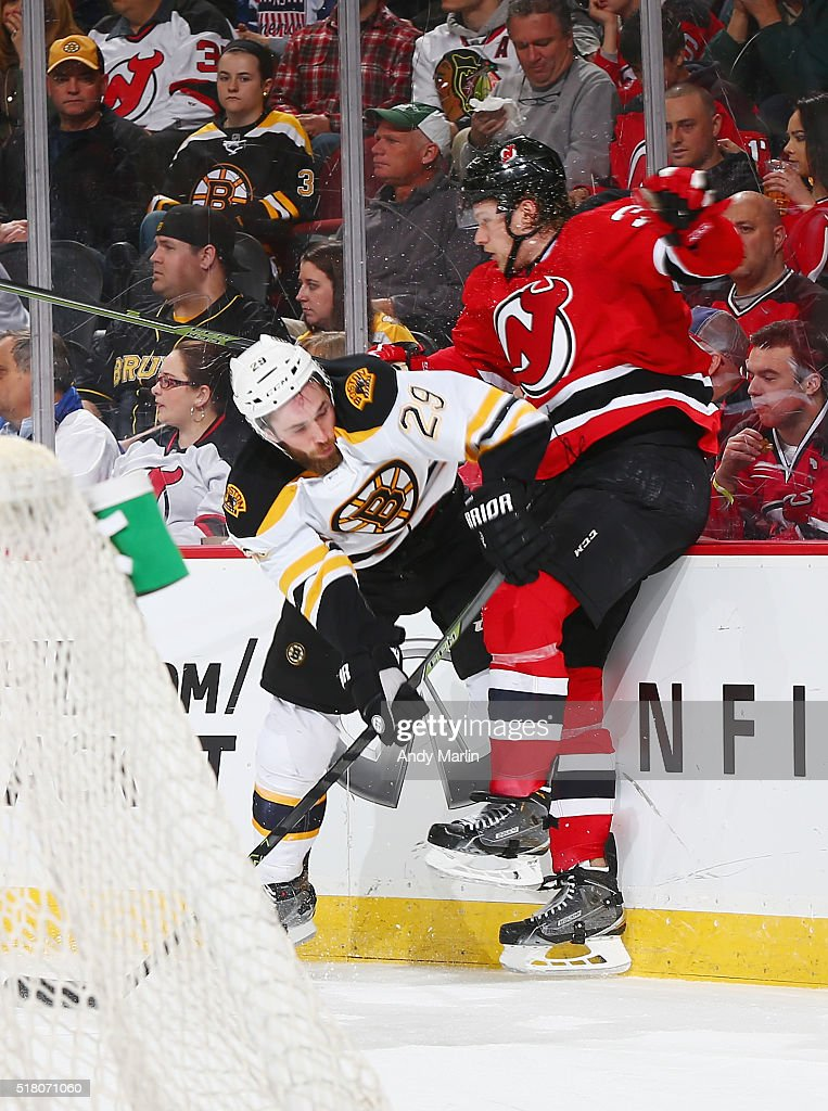 Landon Ferraro #29 of the New Jersey Devils and Seth Helgeson #39 of the Boston Bruins come together at the boards during the game at the Prudential Center on March 29, 2016 in Newark, New Jersey.