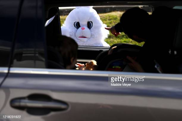 Landon Phillips dressed as the Easter Bunny stands near a car during a drivethrough Easter photo session at StoryHeights Church on April 11 2020 in...