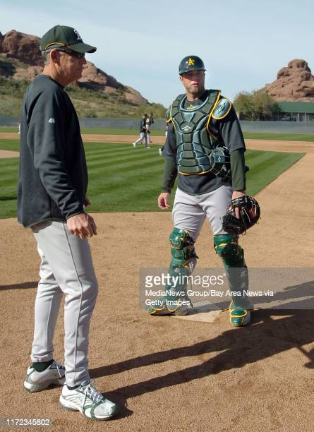 Landon Powell and bullpen coach Ron Romanick discuss drills during the Oakland Athletics spring training camp in Phoenix, Arizona Saturday February...