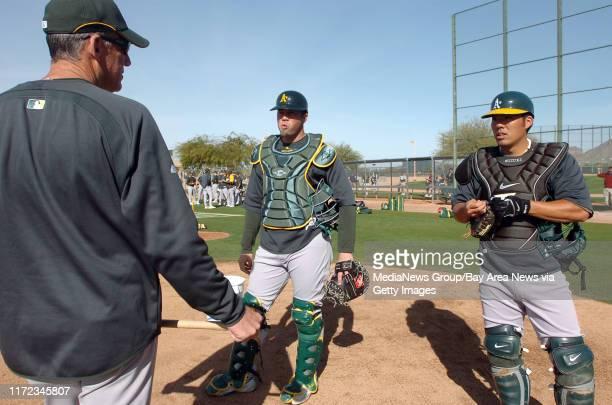 Landon Powell, and Kurt Suzuki listen to bullpen coach Ron Romanick during the Oakland Athletics spring training camp in Phoenix, Arizona Saturday...
