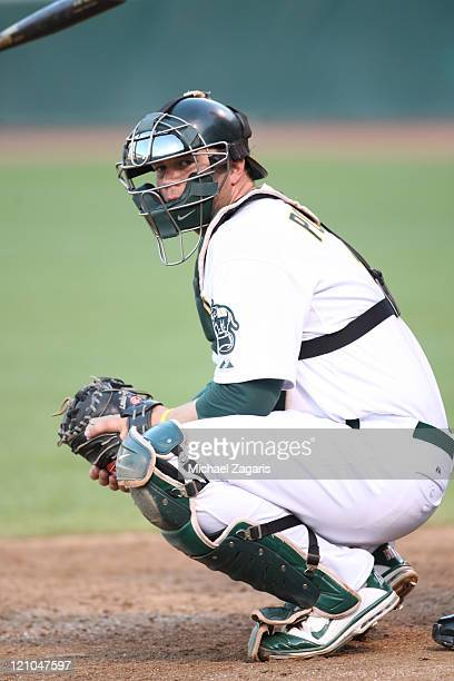 Landon Powell of the Oakland Athletics catches during the game against the Minnesota Twins at the OaklandAlameda County Coliseum on July 30 2011 in...