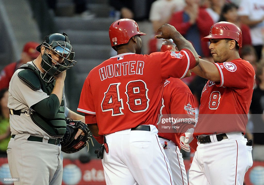 Landon Powell #35 of the Oakland Athletics reacts as Kendry Morales #8 and Torii Hunter #48 of the Los Angeles Angels celebrate a three run homerun during the fourth inning at Angels Stadium on May 15, 2010 in Anaheim, California.